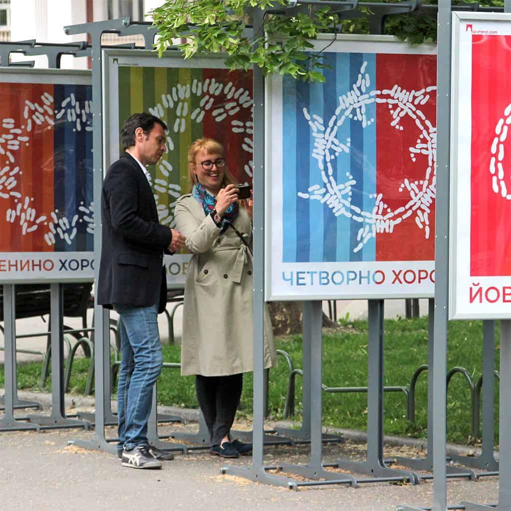 Мъж и жена насочват телефона си, за да оживее изображението от изложбата Последвай стъпките