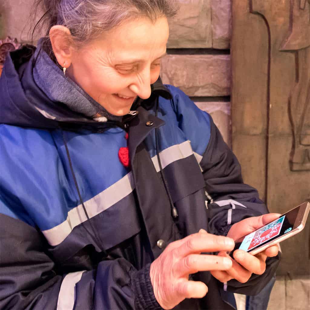 жена е насочила телефона си към изображениет за да оживее хорото от апликацията Таратанци добавена реалност