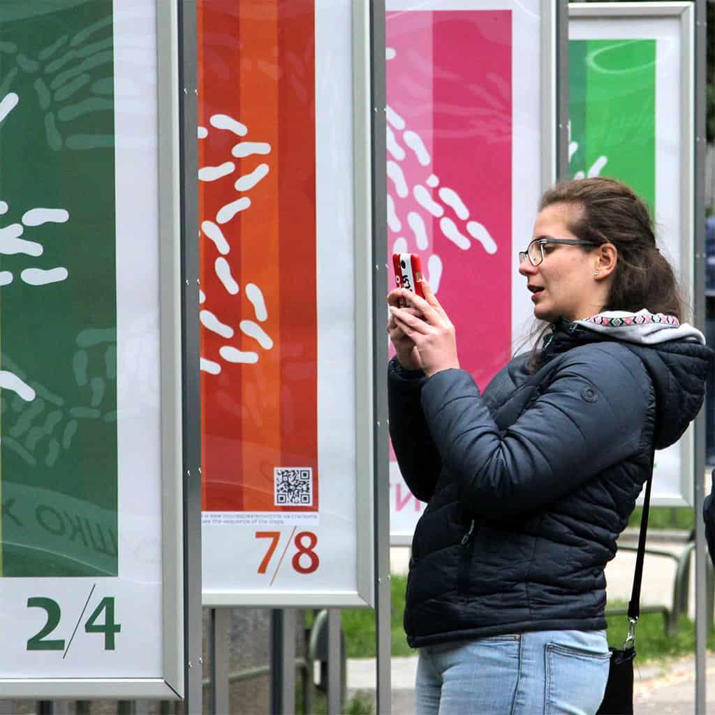 жена сканира изложбата Последвай стъпките, за да оживее хорото от апликацията Таратанци добавена реалност
